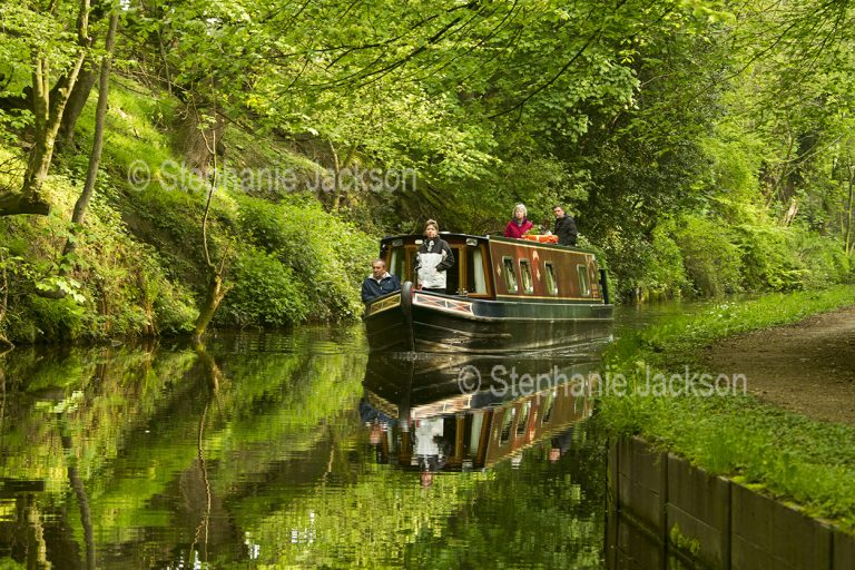 Narrow boat on and reflected in calm waters of a canal hemmed with woodlands in England.