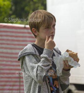 Boy eating hamburger / take away food.
