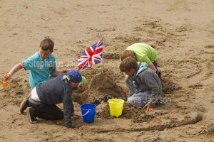 Group of children building sandcastle topped with the English flag, the union jack, on the beach at Whitby in Yorkshire, England.