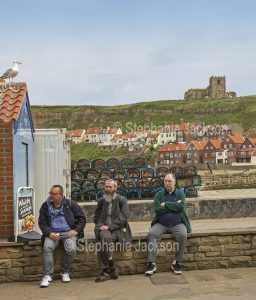 Three men sitting on a stone wall at Whitby in Yorkshire, England.