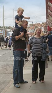 Woman and man carrying young child on his shoulders at Whitby in Yorkshire, England.