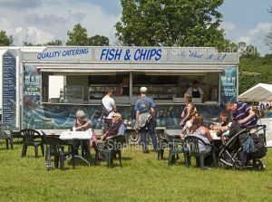 People dining at tables beside mobile fish and chip van at steam fair in England