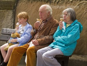 Young girl with grandparents eating ice cream cones at Whitby in Yorkshire, England.