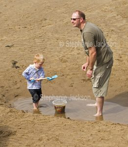 Child with his father playing with bucket and spade in a puddle of water on the beach at Whitby in Yorkshire, England.