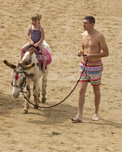 Child riding a donkey on the beach at Whitby in Yorkshire, England.