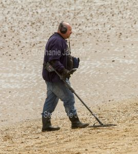 Man using a metal detector on a beach in England.