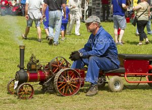 A man sitting on a miniature traction engine at a steam fair in England.