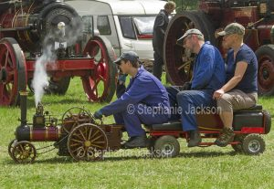 Three men riding on a miniature traction engine at a steam fair in England.