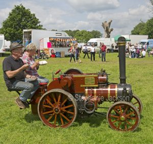 Man and woman eating take-away food while seated on a miniature traction engine at a steam fair in England.