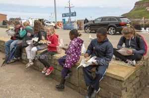 Group of children eating fish and chips from paper wrapping at Whitby in Yorkshire, England.