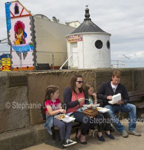 Family, man, woman and two children eating fish and chips from takeaway containers at Whitby in Yorkshire, England.