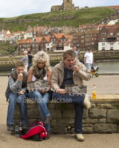 Family, man, woman and boy eating fish and chips from takeaway containers beside the harbour at Whitby in Yorkshire, England.