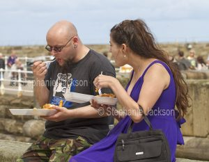 Man and woman eating fish and chips from takeaway containers at Whitby in Yorkshire, England.