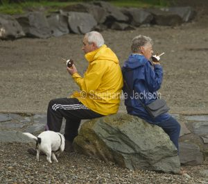 Elderly couple wearing raincoats and sitting on a rock eating ice cream at Coniston in Cumbria, England.