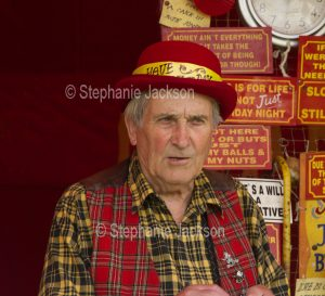 Showman in colourful clothing at a fairground in England.