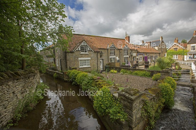 Houses and tea room beside stream at the village of Thornton-le-Dale, also known as Thornton Dale, in North Yorkshire, England.