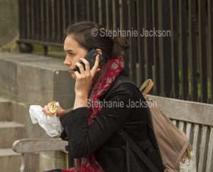 Young woman using a phone while eating lunch and seated on a park bench in Oxford, England.