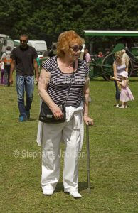Woman using a walking stick at a steam fair in England.