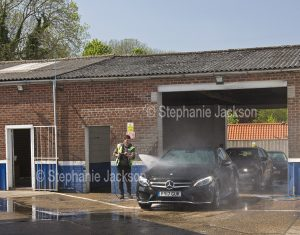 Man washing a car at a car wash in Hull, England.