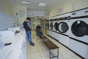 Men waiting in laundromat in England.