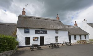 The Black Bull, an historic pub with a thatched roof in the village of Etal in Northumberland England
