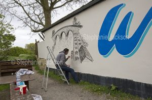 Signwriter at work painting a design on a wall at Arundel in England.