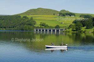 Fishermen in a boat on the calm waters of the lake at Ladybower reservoir in the Upper Derwent Valley, in Derbyshire, England.