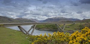 The unique curved Kylesku / Kylescu bridge crosses the lake that's known locally as Loch a' Chairn Bhain near the village of Kylesku in Scotland.