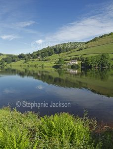 The calm waters of the lake at Ladybower reservoir in the Upper Derwent Valley, in Derbyshire, England.