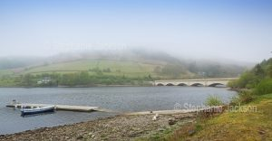 A misty morning over the calm waters of the lake at Ladybower reservoir in the Upper Derwent Valley, in Derbyshire, England