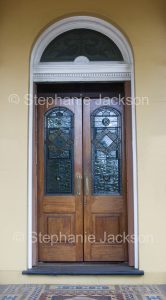 Ornate double wooden doors with stained glass windows and arched entrance to building in NSW Australia
