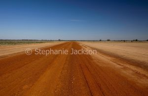 Road crossing the outback plains near Tilpa in NSW Australia.