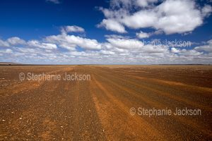 Outback road across vast arid , barren and treeless plains in the outback, Northern Territory, Australia