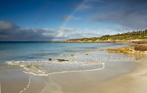 Coastal landscape with rainbow over deserted beach, and blue waters of ocean in Lincoln National Park on Eyre Peninsula South Australia