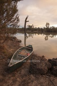 Canoe by The Balonne River at dusk near Saint George in outback Queensland Australia.