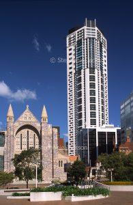 Skyscraper rising beside old church in the city of Brisbane in Queensland Australia.