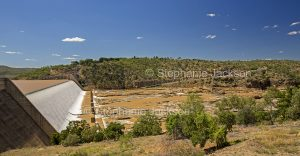 Panoramic view of water of Burdekin River flowing over dam wall and into rocky riverbed in central Queensland Australia.