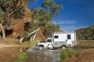 Land Rover campervan crossing Ross River in the East MacDonnell Ranges, in the outback, Central Australia.
