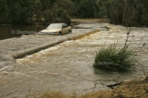 Car being driven through waters of the Kolan River flooding across a road / causeway at Bucca in Queensland Australia.