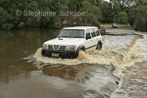 Four wheel drive vehicle / SUV splashing through waters of the Kolan River flooding across a road / causeway at Bucca in Queensland Australia.