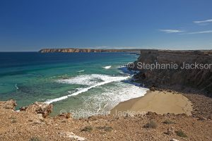 Coastal landscape with cliffs, secluded bay, sandy beach and turquoise waters of ocean near Venus Bay on Eyre Peninsula South Australia