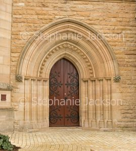 Arched sand stone entrance with door with ornate hinges at Saint Saviour's cathedral / church in the city of Goulburn, NSW Australia