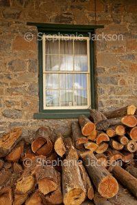 Pile of firewood logs beside cottage windo at Taralga in NSW Australia