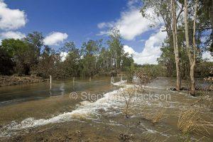 Creek flooding across rural road west of Bundaberg in Queensland Australia.
