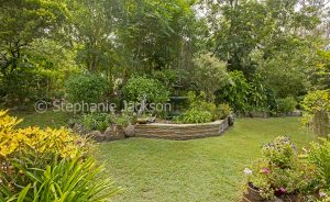 Garden with water feature, stone wall, trees and lawn in Queensland Australia