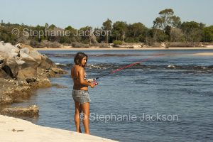 A young girl fishing in a river estuary in NSW Australia