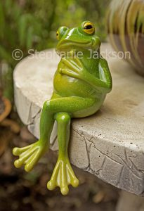 Garden ornament of a green frog in a thinking / contemplative pose.