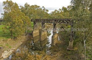 Historic wooden trestle railway bridge over creek and through woodlands at Gundagai in NSW Australia.