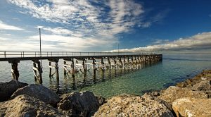Long wooden jetty spearing out into blue waters of ocean at Port Turton on Yorke Peninsula South Australia