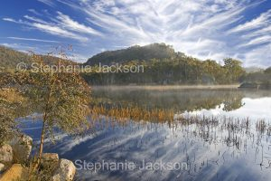 Spectacular Australian landscape with dawn mist rising from lake, with hill, forest, and blue sky streaked with clouds reflected in calm water of wetlands at Dunn's swamp in Wollemi National Park in NSW Australia